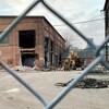 Un vieux bâtiment en briques dont certains pans ont été défaits, de la machinerie est visible tout près.