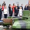 Une quinzaine de personnes dont Emmanuel Macron, Angela Merkel, Jean-Claude Juncker et Jens Stoltenberg regardent  le défilé.