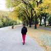 Frances Sreedhar sur un chemin en bord de route bordé par les arbres à l'automne avec les feuilles qui ont déjà commencé à tomber.