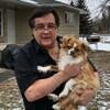 Frank Ostrowski est à l'extérieur de sa maison, il regarde la caméra et tient un petit chien entre ses bras.