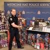 Le policier Cory Both se tient debout entouré des DVD et de figurines saisis.