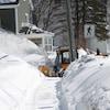 Une souffleuse municipale déblaie la neige sur un trottoir.