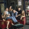 Les acteurs et actrices posent sur un divan.
