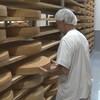 Un fromager tourne d'énormes meules de fromage.