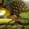 Panier avec des fruits exotiques comme un ananas, des litchis, une goyave et des bananes.