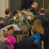 Des hommes transportent un cercueil décoré d'une gerbe de fleurs sur les marches de  la cathédrale. De jeunes parents avec des enfants dans les bras suivent le cortège.