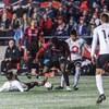 Un joueur est au sol alors que trois autres joueurs continuent d'avancer avec le ballon.