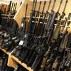 Des carabines AR-15 sont alignées sur une étagère.