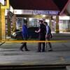 Un policier et deux enquêteurs dans un terrain de stationnement derrière une bannière de police jaune.