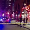 Des véhicules d'urgence sont à l'intérieur d'un périmètre de sécurité, à l'intérieur duquel deux policiers sont en intervention devant un restaurant du marché By.