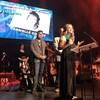 Une jeune femme en robe longue sur une scène lors d'un gala, trophée à la main
