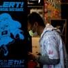 Un homme masqué, au beau milieu d'une partie, dans une salle d'arcade au Japon.