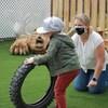 Un enfant joue avec un pneu sous la surveillance d'une éducatrice.