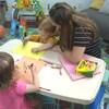 Une éducatrice aide un enfant à dessiner dans une salle de jeux.
