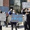 Des éducatrices en grève tiennent des pancartes.