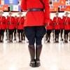 Un agent de la Gendarmerie royale du Canada faisant dos à la caméra, face à un groupe de policiers.