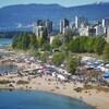 Une vue aérienne d'une plage bondée avec en arrière-plan une vue sur la ville.