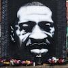 Une murale dépeint le portrait de George Floyd. Des fleurs sont posées tout près.