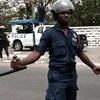 Un policier en uniforme et casqué tient une matraque dans sa main droite.