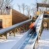 Une structure comprenant deux glissoires pour des toboggans installée dans un parc en hiver.