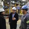 Alain Paul parle avec deux autres personnes qui portent un casque de protection.