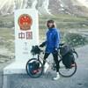 Un homme sur son vélo pose devant un monolithe devant une montagne.