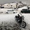 Une moto et des voitures sont garées dans une rue de Calgary remplie de grêlons.
