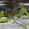 Une pelle mécanique flottante verte brise la glace dans la rivière.