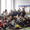 Des dizaines d'étudiants sont assis par terre ou autour de bureaux. Ils sont majoritairement souriants et tapent des mains.