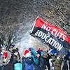Des enseignants en grève tiennent un drapeau géant qui dit : « pas de coupes en éducation ».
