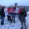 Des grévistes qui tiennent des pancartes et des bannières où il est marqué « en grève » et « aucune coupure en éducation ».