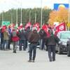Un groupe de travailleurs, de dos, agitent des drapeaux à l'effigie de leur syndicat.
