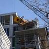Deux travailleurs dans une nacelle près du toit de l'immeuble où un morceau de grue de construction jaune est écrasée.