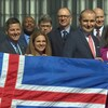 Une dizaine de personnes en complets et vêtements chics, derrière un grand drapeau islandais. Les personnes à l'avant-plan (le maire, le président islandais et leurs épouses respectives) tiennent le haut du drapeau.