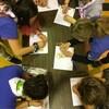 Plusieurs jeunes filles participent autour d'une table à une activité manuelle.
