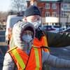 Deux bénévoles qui portent le masque et la visière récoltent les dons sur la rue Saint-Germain Ouest à Rimouski.