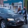 Deux bénévoles s'approchent d'une voiture.