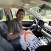 Un homme est dans sa voiture et tient une pancarte où il est inscrit ''Ça va bien aller.''