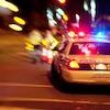Zoom sur une auto-patrouille du Service de police de Montréal dans la nuit, en été. Modèle désuet de Ford Crown Victoria.