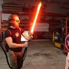 Un homme tient un sabre-laser devant un Stormtrooper de Star Wars.