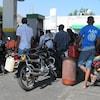 Des hommes avec leur motocyclette font la file à une station service en plein jour.