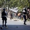 Deux hommes armés patrouillent dans une rue où des gens fuient en courant