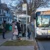 Quatre personnes montent à bord d'un autobus par la porte avant.