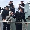 Deux officiers descendent une passerelle en portant le trophée.