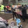 Des agents ont des tentes dans leurs mains et les traînent sur le pavé