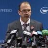 Un homme en conférence de presse avec les micros des grands réseaux posés sur son lutrin.
