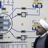 Le président iranien, portant la barbe mi-longue, des lunettes et un chapeau enturbanné, observe un mur où figure un diagramme et des cadrans analogiques.