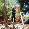 Un enfant sur une module en bois surélevé tient une corde.