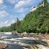 Un hélicoptère de la Sûreté du Québec survole une rivière à la hauteur de la cime des arbres.