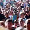 Un homme qui poste une camisole et un bandeau multicolores est au milieu d'une foule, les bras en l'air, les doigts qui forment un V.